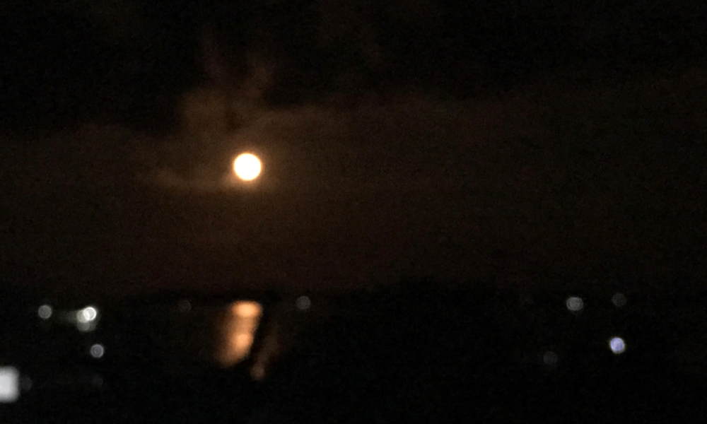 distorted image of a red moon shining over the sea