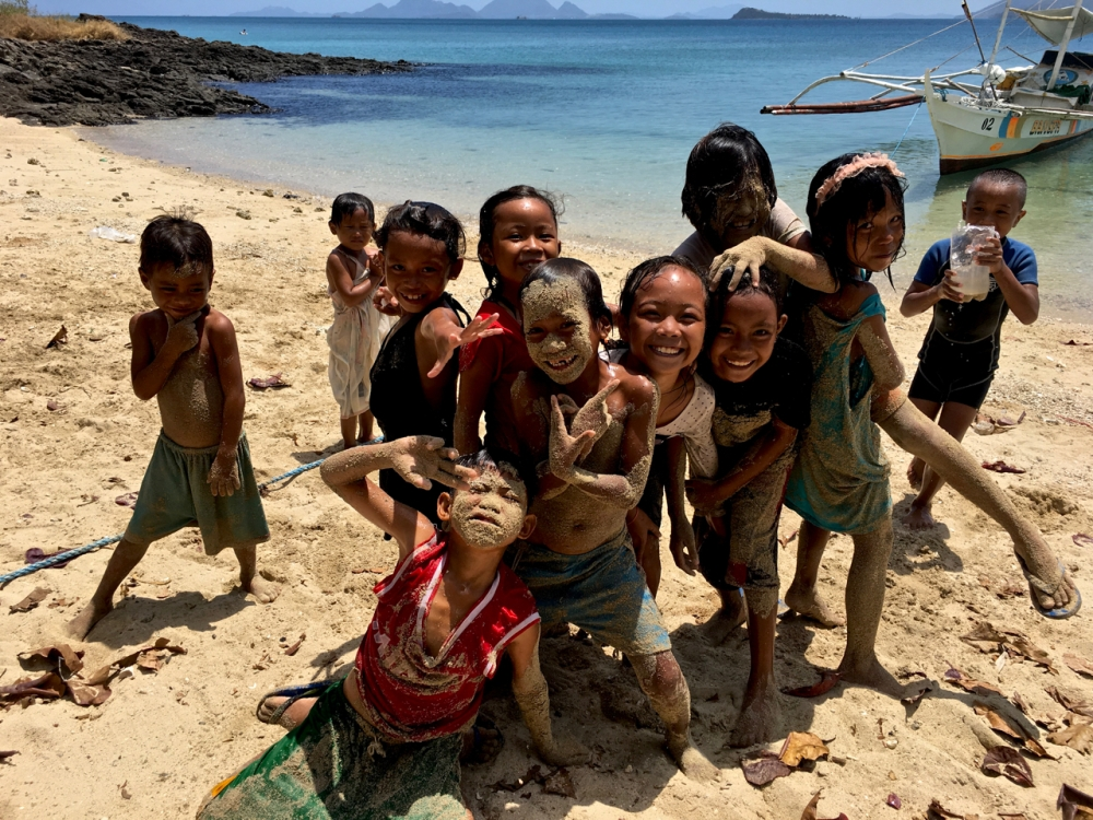 impoverished island kids of the Philippines covered in sand